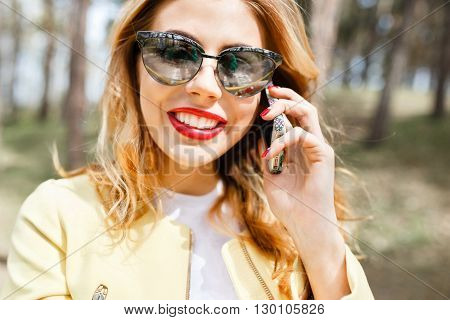 Beautiful stylish girl on a sunny day in the park talking on the phone on the background of trees.