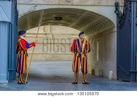VATICAN, ITALY - JUNE 13, 2015: Swiss guard outside of Saint Peter Basilica at Vatican. Striped uniform considered one of oldest military clothing. Vatican colors