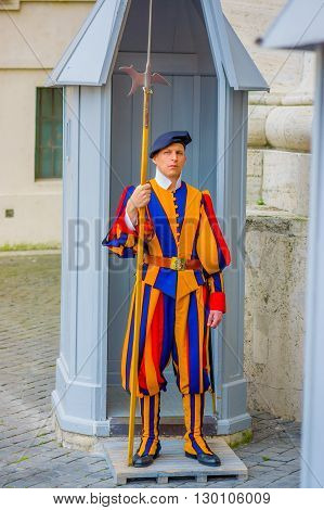 VATICAN, ITALY - JUNE 13, 2015: Swiss guard outside of Basilica at Vatican. Colorful and striped uniform considered one of oldest military clothing around the world.