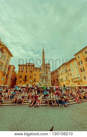 ROME, ITALY - JUNE 13, 2015: Piazza della Rotonda square outside of Parthenon of Agrippa, people resting and taking a break on the fountaine.
