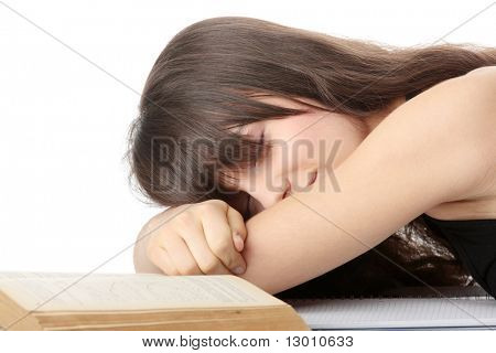Sleeping while learning - tired teen woman sleeping on desk, over white background