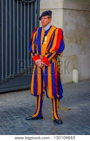 VATICAN, ITALY - JUNE 13, 2015: Man with typical uniform of swiss guard at Vatican country, colorful striped.