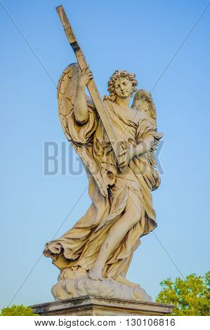 ROME, ITALY - JUNE 13, 2015: Stone sculture in Rome, angel with wings holding a cross.