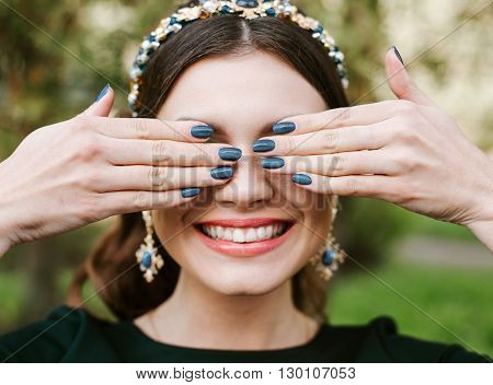 Fashion, beauty, tenderness, manicure. Young happy woman bright manicure smile wide, white smile, straight white teeth. The girl covers her face with her hands. Hair band, earrings, blue Polish.