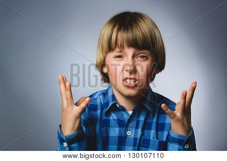 Portrait of angry boy in blue shirt with hands up yelling isolated on gray studio background. Negative human emotion, facial expression. Closeup.