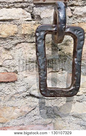 the old iron hinge or arm is intended for mooring of boats and placed on a stone wall closeup