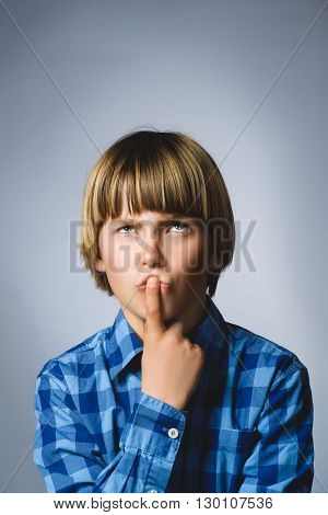Close up Thoughtful Young Boy Looking Up with Hand on the Face Against Gray Background with Copy Space.