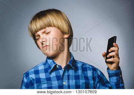 Closeup Portrait of worried stressed boy with mobile going irritation on gray background.