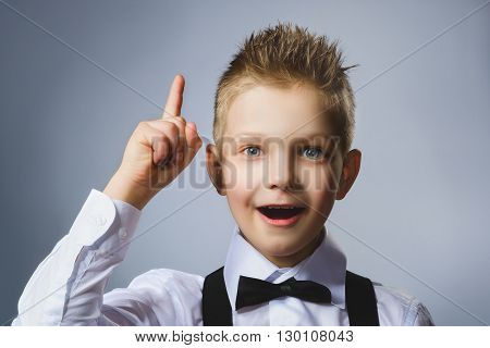Closeup Portrait of gestured child  on grey background. Boy found the idea or solution.