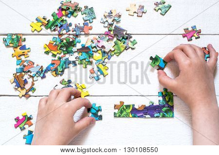 Child collects a picture from puzzles. Multicolored puzzle scattered on white wooden table