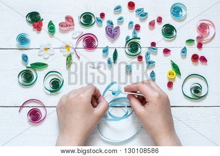 The child twists blanks for quilling. Many details of quilling laid on a white wooden table
