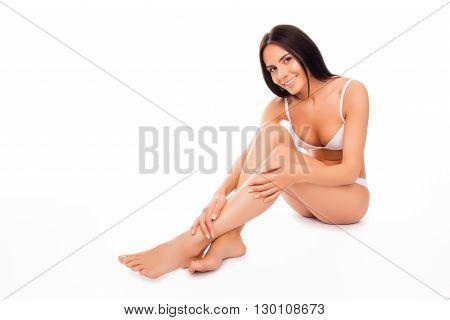 Pretty Woman In White Underwear Doing Massage For Her Legs