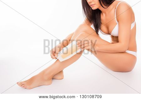Close Up Portrait Of Young Woman Shaving Her Leg With Wax Stripe