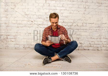 Happy Man Sitting On Floor With Crossed Legs And Tablet