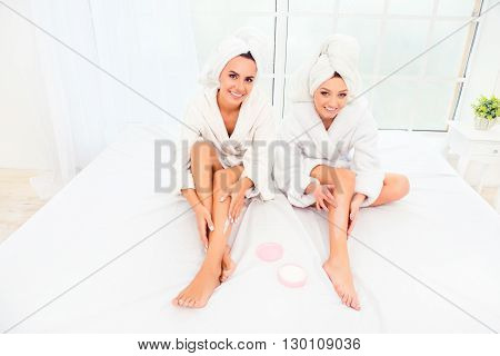 Happy Sisters In Bathrobes And Towels On Heads Applying Cream On Legs