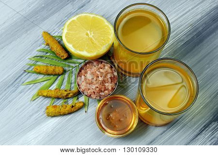 Spicy healthy Haldi or Turmeric lemon Himalayan salt and Honey antioxidant drink with lemon on a moody background.