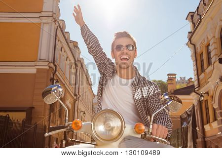 Cheerful young man ridding a bike with raised hand