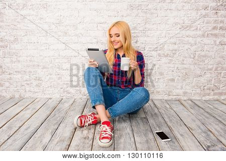 Young Woman Sitting With Crossed Legs And Holding Tablet And Cup