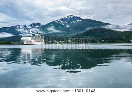 Cruise ship docked in Juneau, Alaska with cloudy skies and snow capped mountain in background