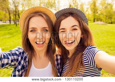 Beautiful women making selfie winking and showing tongue