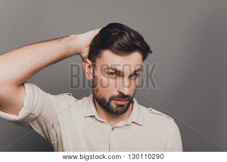 Portrait Of Handsome Serious Young Man Combing His Hair
