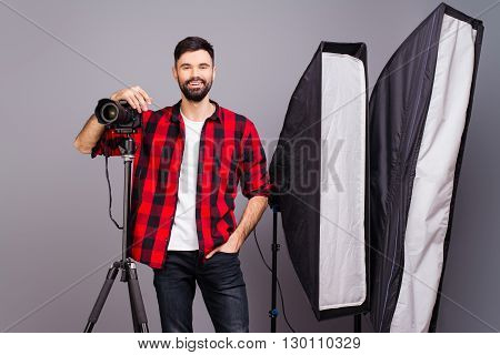 Young Smiling Photographer With Camera In Professionally Equipped Studio.