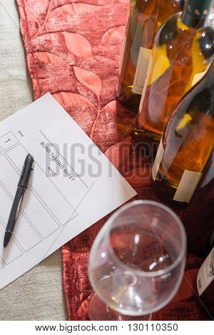 A row of wine bottles and an empty wineglass by a blank blind tasting form and pen on velvet.