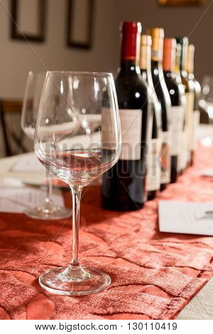 An empty wineglass in front of a row in bottles of wine on velvet-covered table.