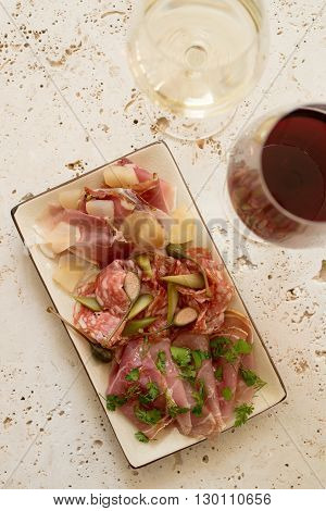 A plate of various deli meat and greens alongside two glasses of wine