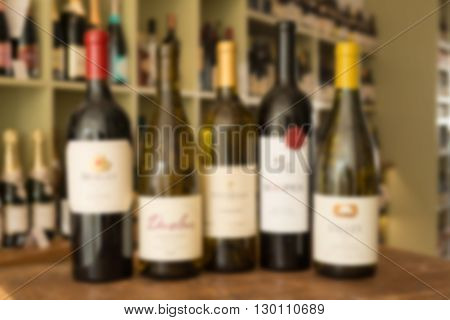 Blurred photo of a row of five wine bottles and a wine collection in the background