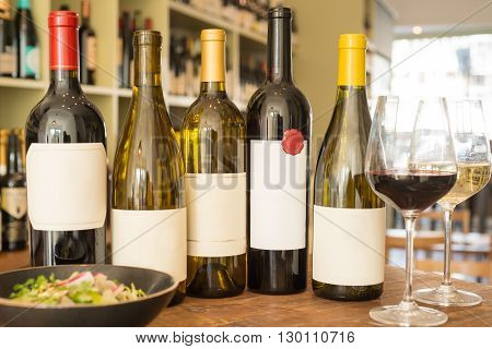 A group of wine bottles with blurred out labels alongside a couple of wineglasses and a bowl of salad with a wine collection in the background