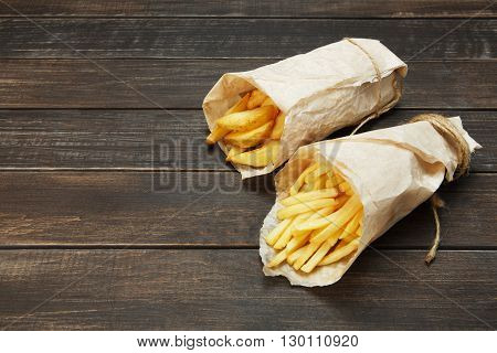 Tasty potato wedges and french fries wrapped into brown kraft wrapping paper. Fast food take away at rustic wooden boards background. Choice of fried potatoes at wood. Chips, potato slices. Top view