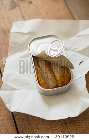 A slightly opened can of sardines or herring in oil on a piece of paper