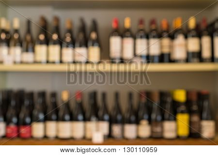 Blurred image of two rows of wine bottles