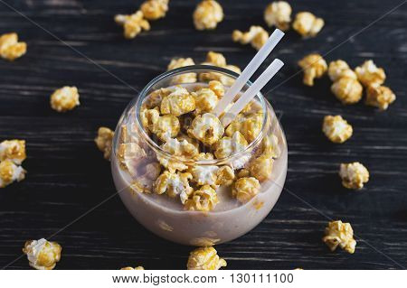 Cup of cacao with caramel popcorn on wooden table . Unhealthy food