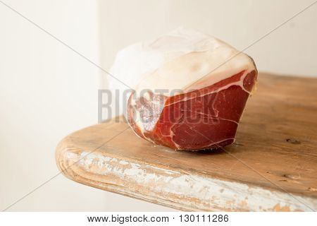 A block of ham or deli meat on a wooden counter