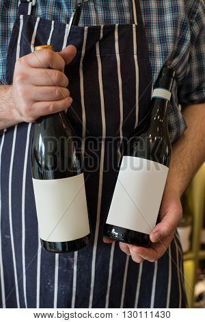 A person with a bottle of unlabeled wine in each hand.