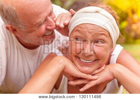 whispering smiling older couple