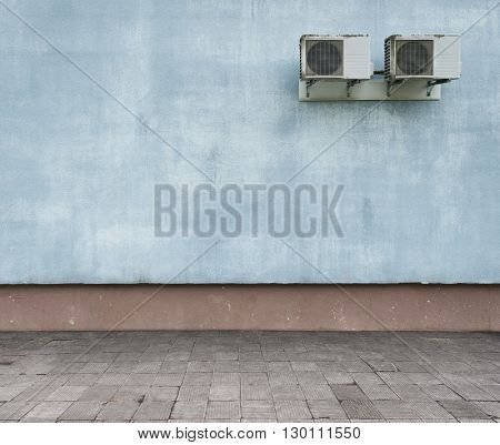 Urban background. Grunge obsolete street wall and weathered pavement.