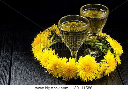 Original homemade dandelion wine in old wineglasses and wreath from dandelions on a dark background