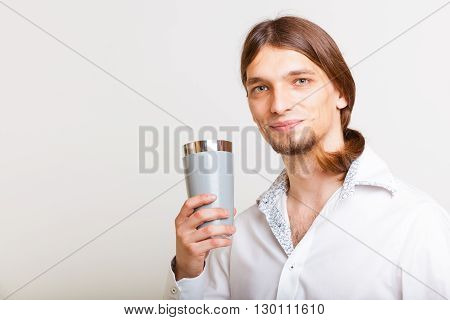 Alcohol liquor drinking relax party concept. Male barman makes cocktail. Young bartender holding glasses making drink.
