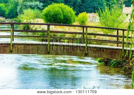 Old small bridge over river stream creek in green garden. Nature and landscape.