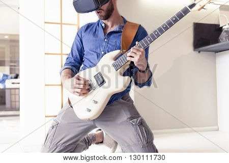 Young Adult Playing Guitar At Home Using Viewer For Augmented Re