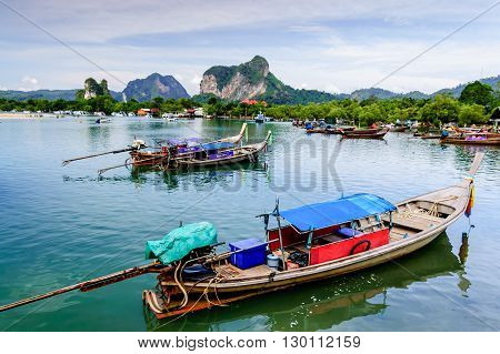 Hat Noppharat Thara Thailand - January 5 2013: Long-tail boats for fishing & tourist trips moored in bay with limestone karsts on horizon at Hat Noppharat Thara in Krabi Province southern Thailand