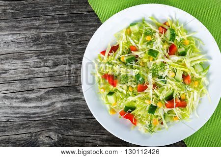 Healthy low calories spring coleslaw salad with bell pepper corn cucumber and dill on a white dish on an wooden table studio lights close-up top view