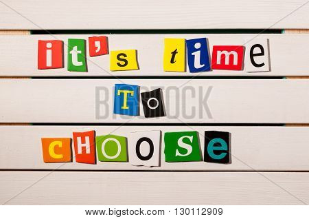 It's time to choose - written with color magazine letter clippings on wooden board. Concept  image.