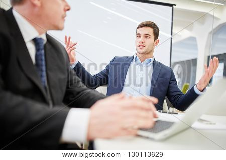 Two businessmen in a dialogue about consulting in the office
