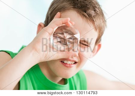 Boy Holding A Multi Faceted Crystal Against Eye