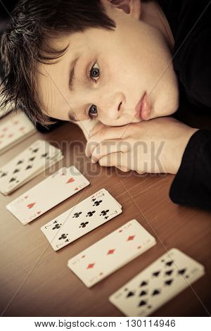 Sad Boy Lays His Head On Table By Row Of Cards