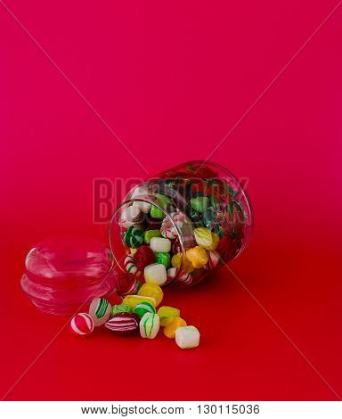 Glass jar with small colored candies spilled on a red background.